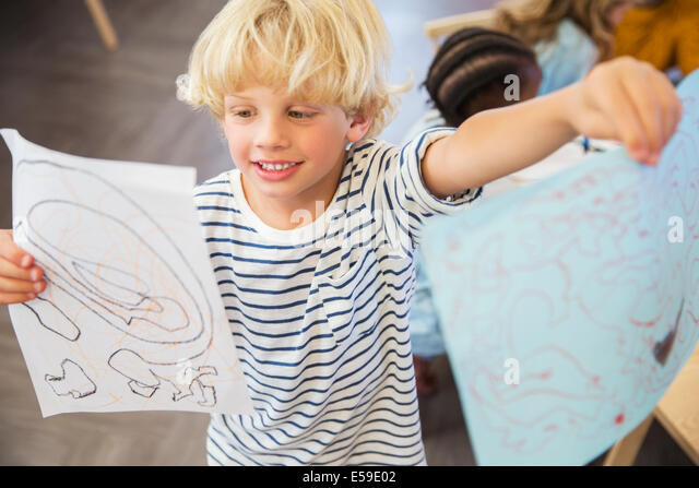 Student showing off drawings in classroom - Stock-Bilder