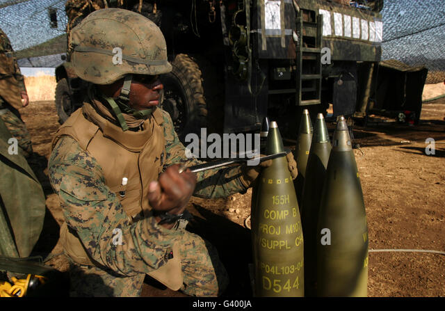 An artilleryman places a fuse on a 155mm projectile using an M18 fuse setter. - Stock Image