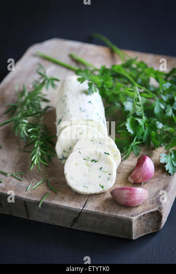 Butter flavored with herbs and garlic - Stock Image