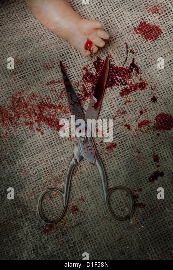 scissors with blood and the hand of a doll - Stock Image