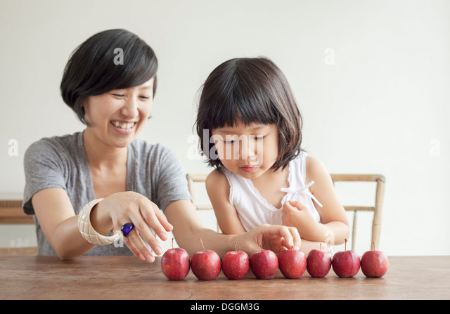 Mother and daughter with red apples in a row - Stock Image