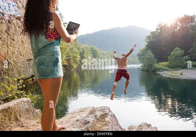 Woman photographing boyfriend jumping from rock ledge, Hamburg, Pennsylvania, USA - Stock-Bilder