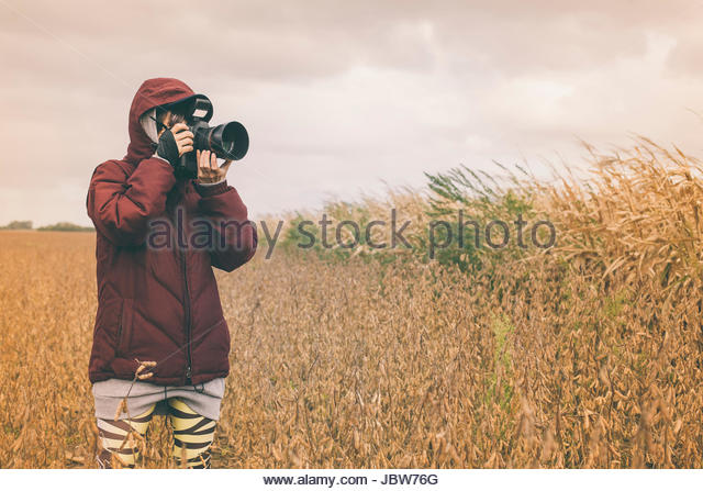 Mid adult woman, standing in field, taking photograph with SLR camera with long lens - Stock-Bilder