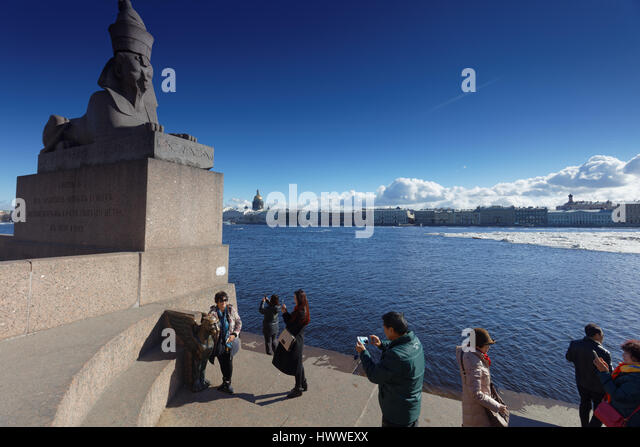 St. Petersburg, Russia, 23rd March, 2017. Chinese tourists make photos against the sphinx on the embankment of river - Stock Image