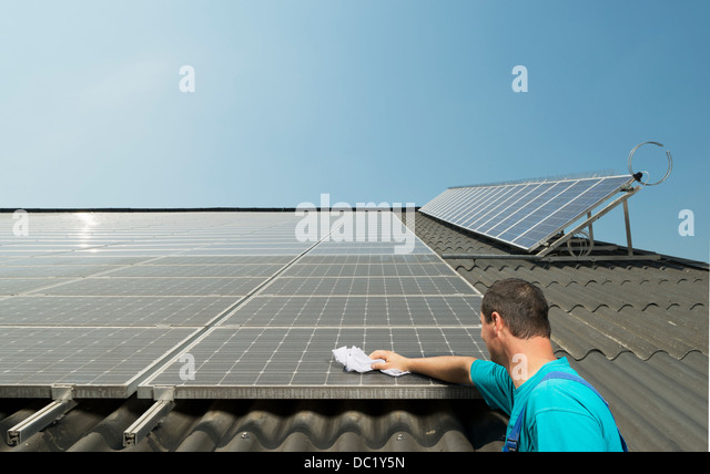 Farmer cleaning solar panels on barn roof, Waldfeucht-Bocket, Germany - Stock Image
