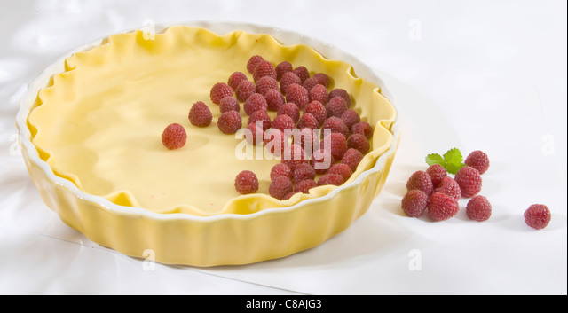Uncooked pastry in the mould and raspberries - Stock Image