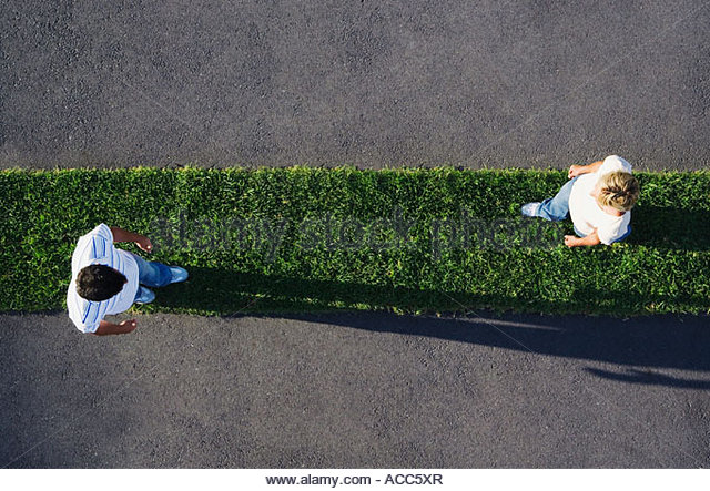 Woman and man walking on grass strip with pavement - Stock Image
