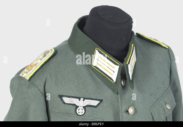 A uniform ensemble for a field postal inspector., A field grey gabardine tunic with dark green collar (moth holes), - Stock Image