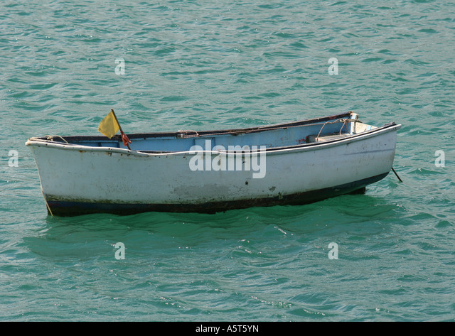 Empty rowboat in water - Stock Image