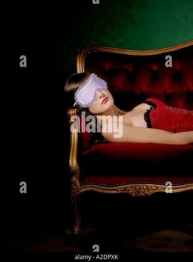 1217985 indoor flat room livingroom young woman 25 30 brunette red top corset lie sofa couch rest relax sleep cover - Stock-Bilder