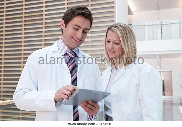 Doctors in lab coats using digital tablet in hospital corridor - Stock Image