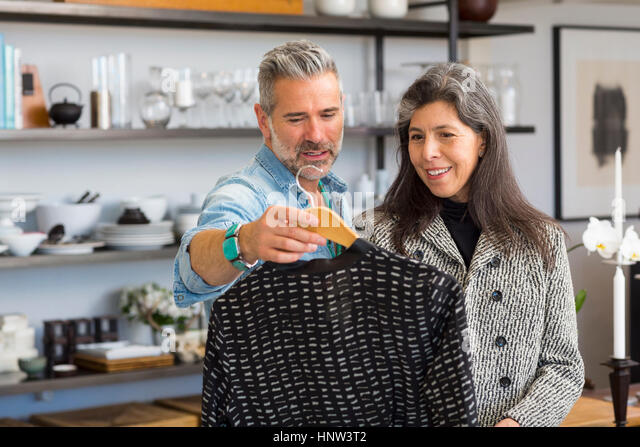 Man showing sweater to woman in store - Stock-Bilder
