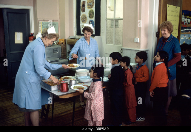 Archival image of dinner ladies wearing nurses white caps serving Asian primary students in London inner city school - Stock Image