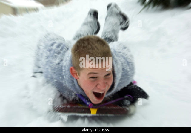 Teenage male sledding down hill - Stock-Bilder