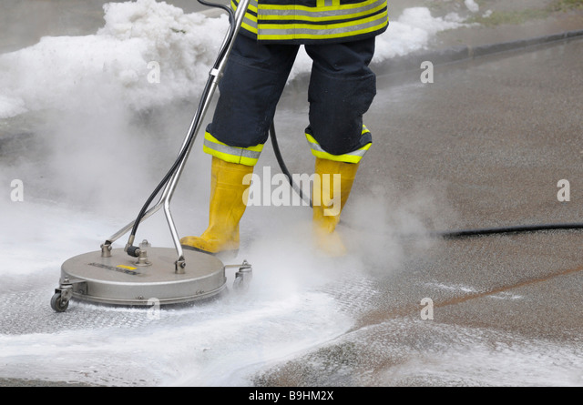 Fireman neutralising leaked brake fluid from a street with cleaning equipment - Stock Image