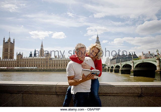 A middle-aged couple in front of the Houses of Parliament, looking at a guidebook - Stock Image