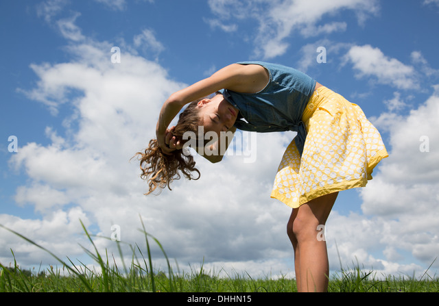 Teenage girl bending forward with hands in hair - Stock Image
