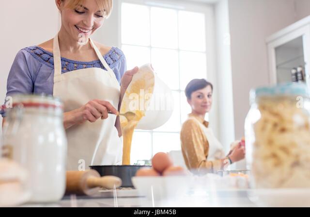 Female caterers baking, pouring cake batter into tin in kitchen - Stock-Bilder