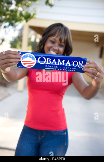 african american teenager holding Obama presidential campaign sticker and smiling - Stock Image