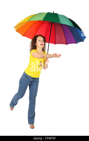 young beauty woman in yellow shirt with multicolored umbrella jumping with reached out a hand isolated on white - Stock Image