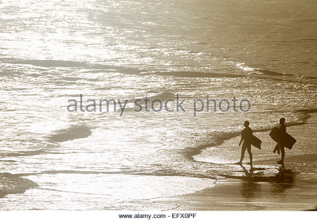 Two Men holding body boards walking out to sea - Stock Image