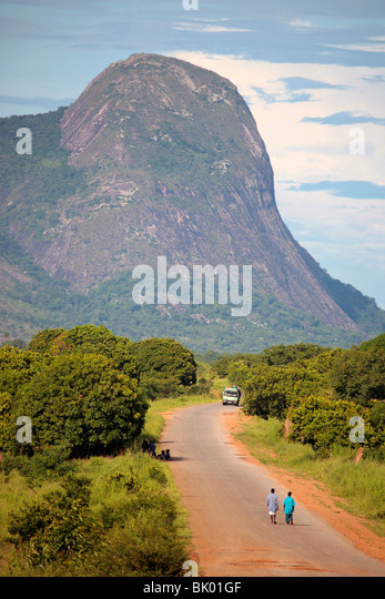 Landscape of Northern Mozambique with inselberg and macadam road - Stock Image
