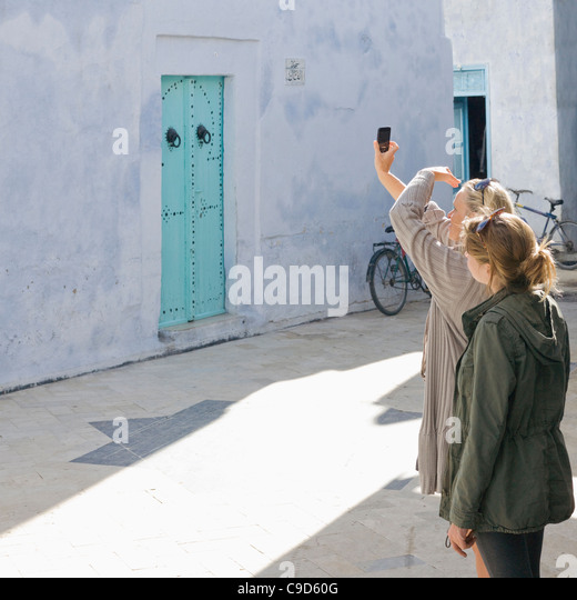 Tunisia, Kairouan, mother and daughter taking picture with cell phone - Stock-Bilder