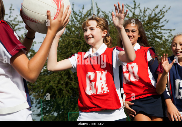 Schoolgirl netball players defending - Stock Image
