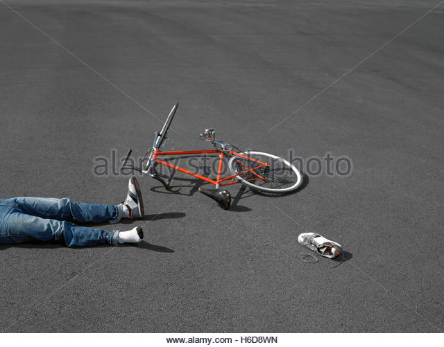 Legs of bike rider with crashed bicycle on asphalt. - Stock Image