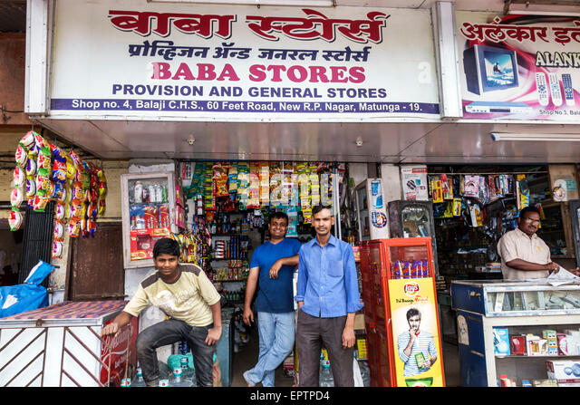 India Asian Mumbai Dharavi 60 Feet Road small businesses business convenience store front sale man owner manager - Stock Image