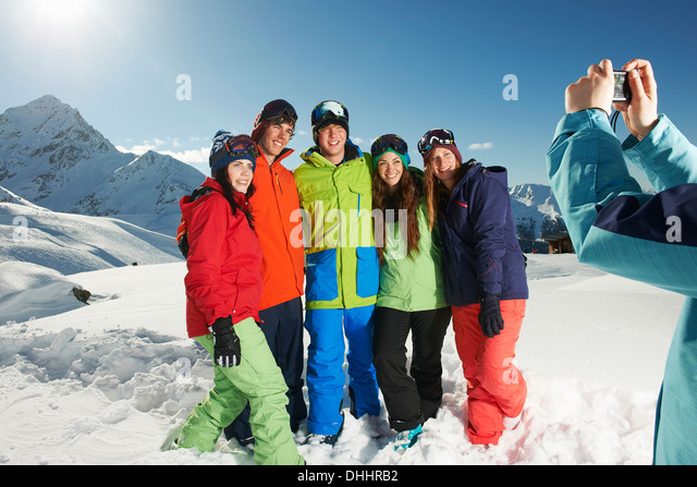 Young woman photographing friends, Kuhtai, Austria - Stock Image
