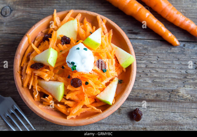 Carrot and apple salad with raisins, yogurt and herbs in rustic ceramic bowl, copy space - Stock Image