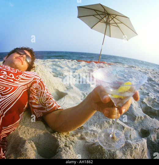 Young man drinking Martini on beach - Stock Image
