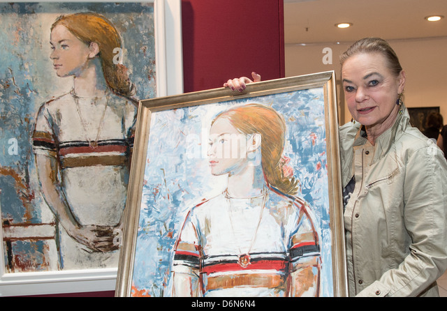 Berlin, Germany, the former figure skater Gabriele Seyfert with a protrait painted by Bert Heller - Stock Image