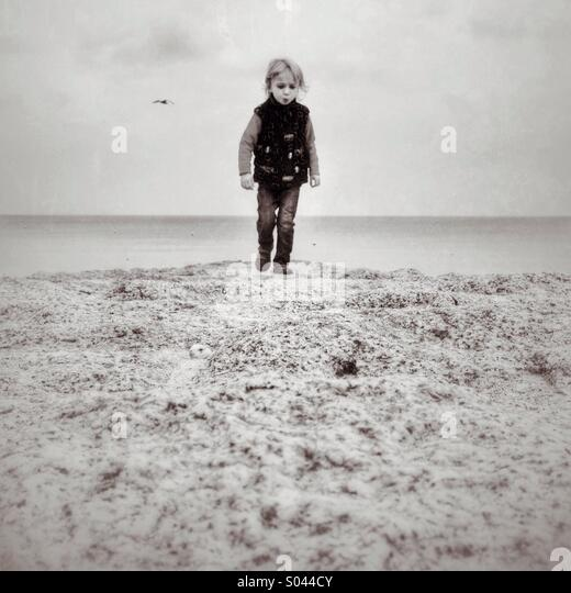 Boy on a stone path by the sea at Dawlish - Stock Image