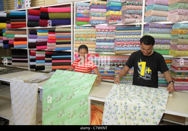 Nicaragua Granada Calle Atravesada shopping market store business fabrics textiles counter display Hispanic man - Stock Image