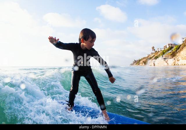 Young boy surfing wave, Encinitas, California, USA - Stock Image
