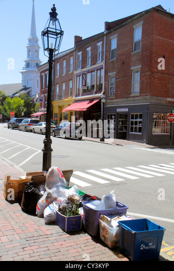 New Hampshire Portsmouth Market Street businesses trash containers curbside curb sidewalk flattened cardboard boxes - Stock Image