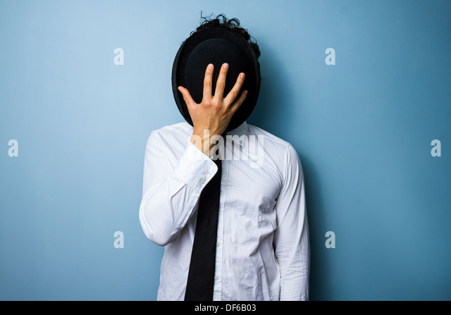 Young man hiding his face behind his bowler hat - Stock Image
