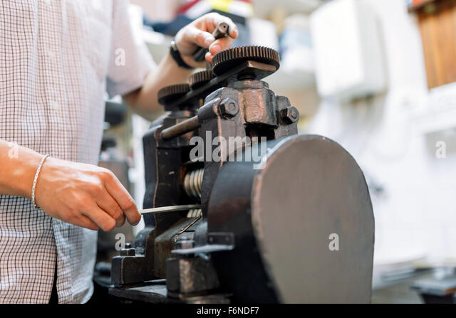 Goldsmith crafting metal with the help of a press - Stock Image