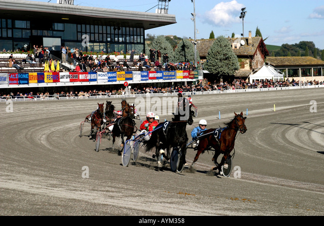 Trotting horse race at the Ippodromo di San Paolo di Montegiogio Le March Italy with typical Le Marche hill town - Stock Image