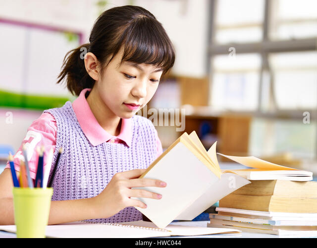 asian primary school pupil reading a book in classroom. - Stock Image