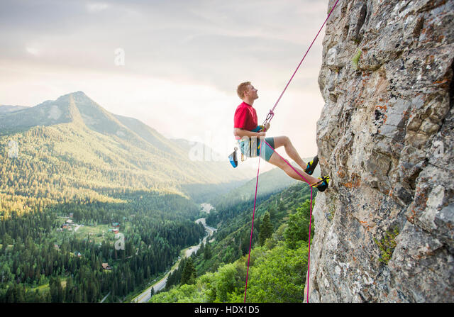 Caucasian man rock climbing - Stock Image