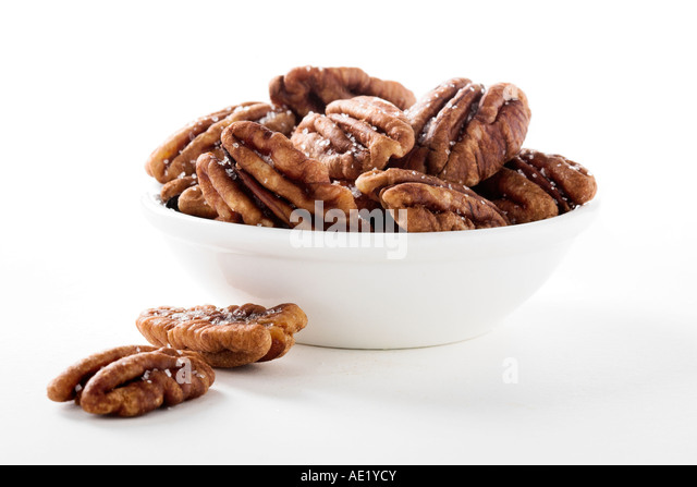A bowl of salted pecans with white background cutout - Stock Image