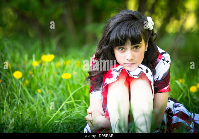 Portrait of a teen girl sitting in the grass - Stock Image
