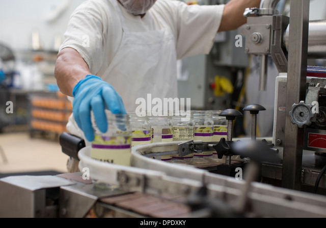 Man handling glass jars on production line - Stock Image