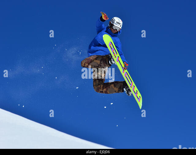 VERBIER, SWITZERLAND - FEBRUARY 21: Freestyle snowboarder performing rear grab stunt and trailing snow:  February - Stock-Bilder