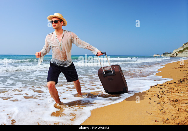 A tourist carrying a suitcase at the beach Peroulades at Corfu island, Greece - Stock-Bilder