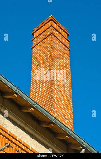 Tall red brick house chimney - France. - Stock Image