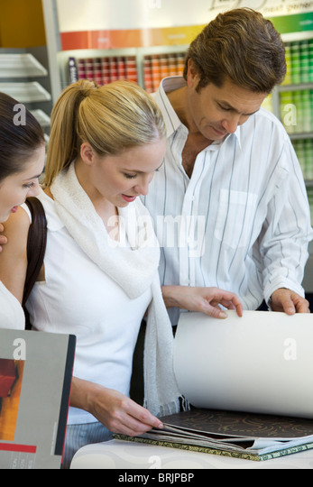 Couple looking at wallpaper samples in store - Stock Image